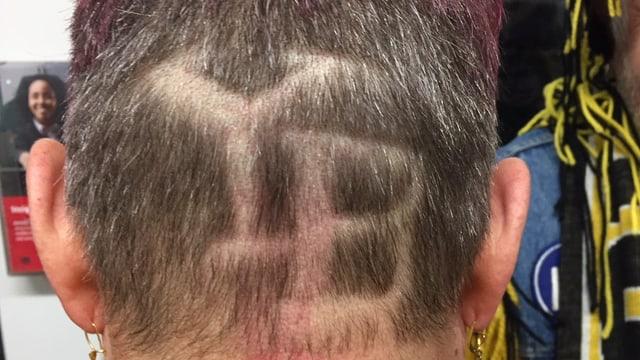 Die Buchstaben YB ins Haar rasiert.