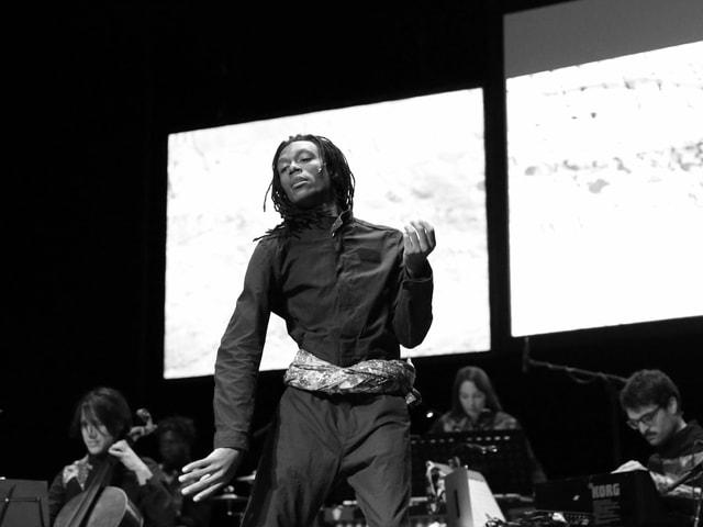 Mann mit dunkler Hautfarbe und Dreadlocks steht auf der Bühne in der Mitte in tanzender Pose, hinter ihm ein kleines Streichorchester.