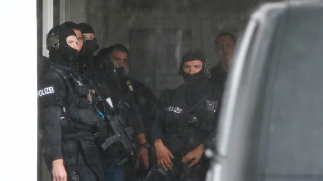 Maskierte Polizisten in einem Hauseingang.