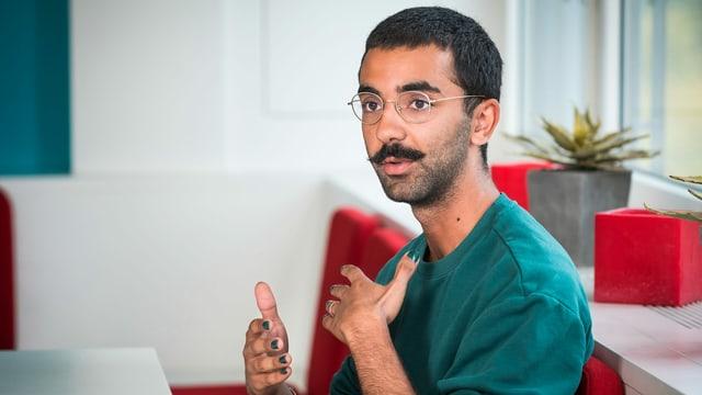 Ein junger Mann mit dunklen Haaren, Schnurrbart und lackierten Fingernägeln.