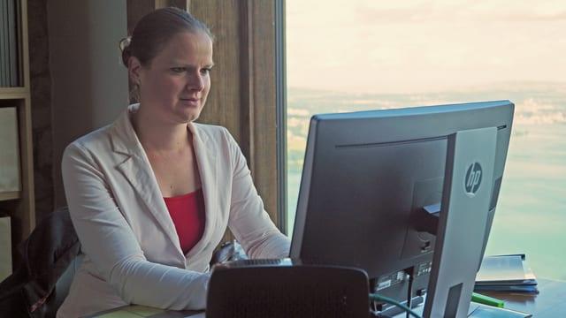 Eine Frau sitzt an einem Computer und schreibt.