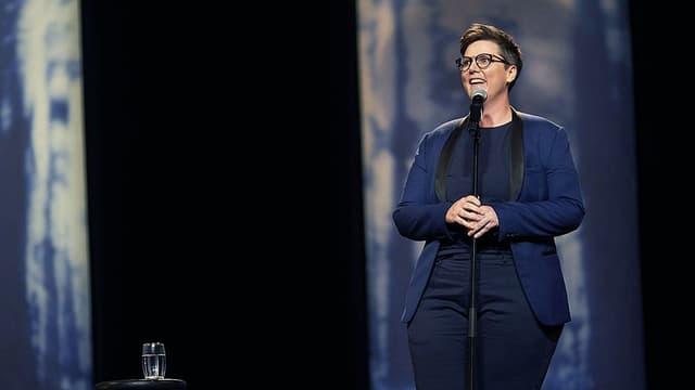 Eine Frau steht im blauen Blazer auf der Bühne vor einem Mikrofon.