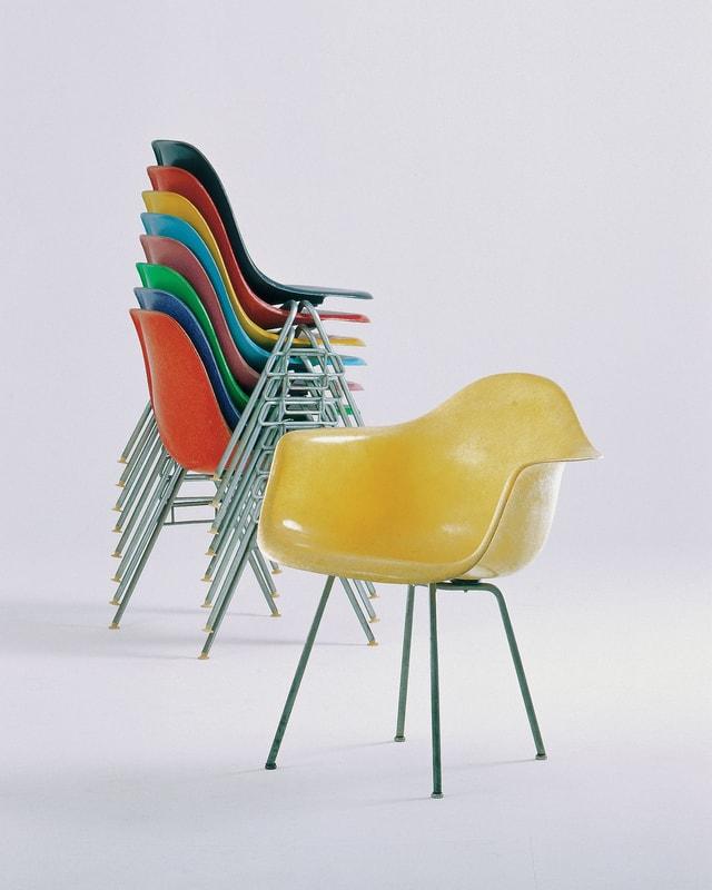 Im Hintergrund gestapelte Fiberglas-Stühle ohne Armlehnen, im Vordergrund ein Fiberglas-Stuhl mit Armlehne.