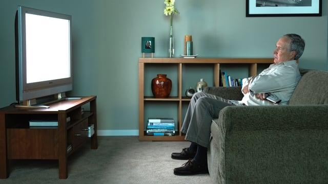 Ein Mann sitzt auf einem Sofa und schaut fern.