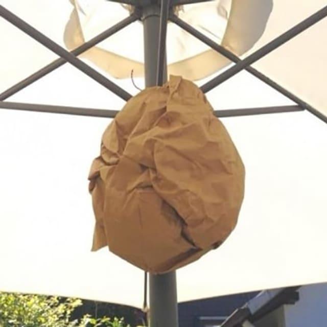 Brauner, zerknüllter Papiersack unter einem Sonnenschirm aufgehängt.