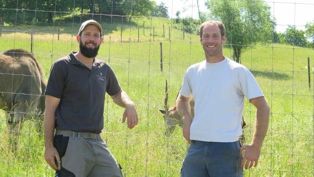Zwei Männer stehen vor Zaun, dahinter Weide .