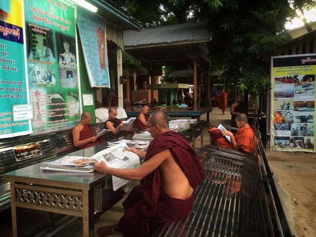 Mönche in einem buddhistischen Kloster in Burma. Sie sitzen am Tisch und lesen Zeitung.
