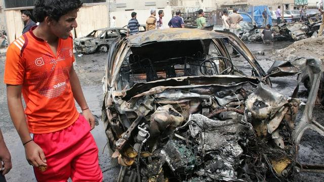 Ein Mann in roter Sportkleidung betrachtet ein zerbombtes Auto.