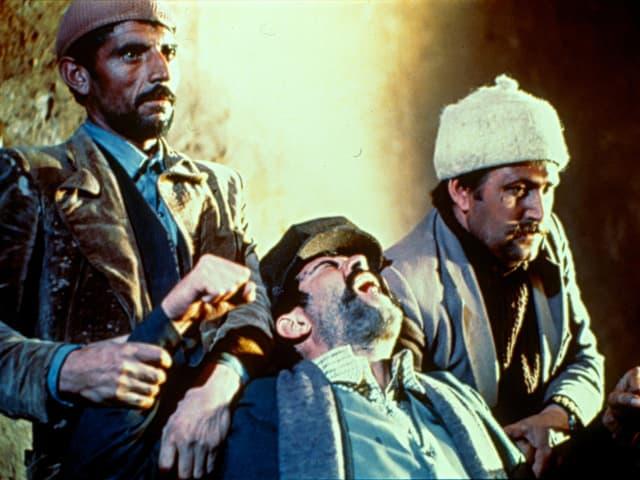 Filmstill: Zwei Männer halten ein Mann, der sich verzweifelt wehrt.