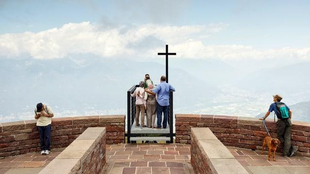 Touristen stehen beim Kreuz einer Aussichtsplattform und machen Fotos.