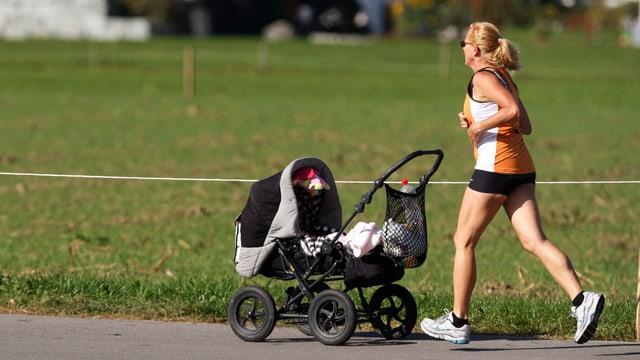 Frau joggt mit Kinderwagen bei Sonnenschein.