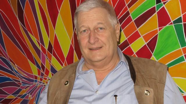 Theo Meyer steht vor einem Bild, das aus verschiedenen geometrischen Flächen besteht. Es dominieren die Farben gelb und rot.