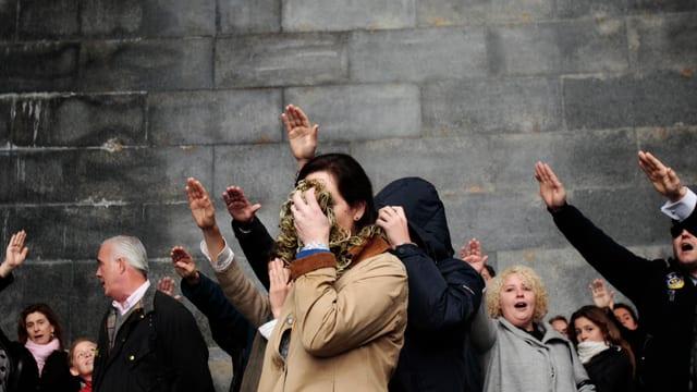 Mehrere Personen mit Faschistengruss stehen vor einer grauen Wand, eine Frau verdeckt ihr Gesicht.