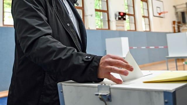 ina persuna che bitta gist ina brev da votar en in'urna.