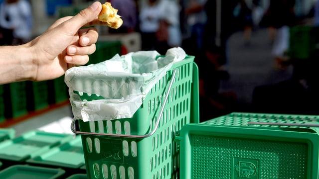 Eine Hand wirft ein Apfelgehäuse in eine mit Tüte bespannte, grüne Kompostbox.