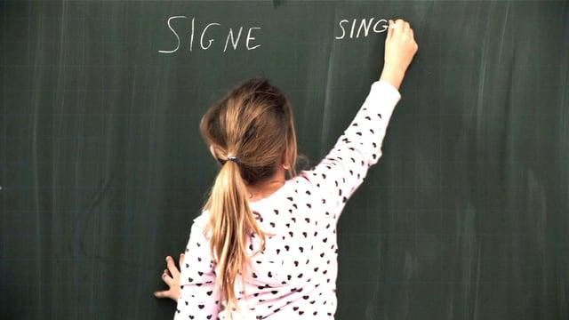 Ein Kind schreibt mit Kreide an die Tafel das Wort «Signe».