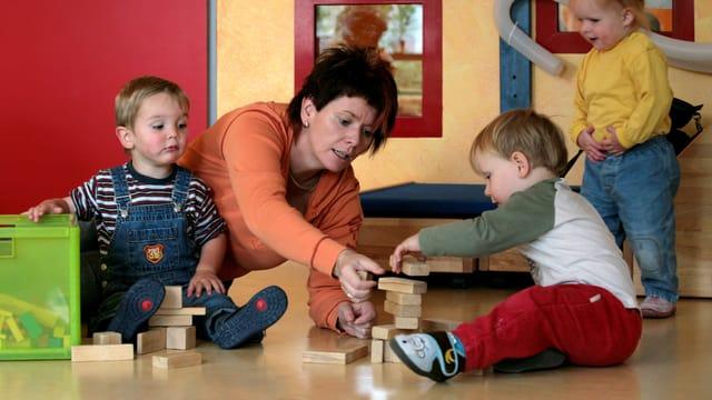 Eine Frau spielt mit Kindern am Boden