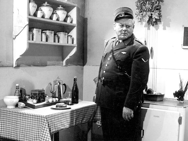Ein Mann in Uniform steht in einer Küche.