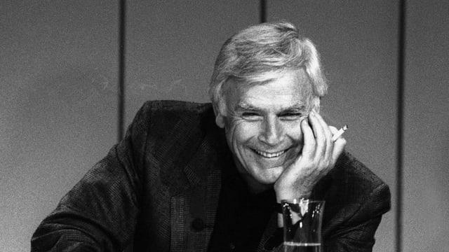 Joachim Fuchsberger lachend mit einer Zigarette in der Hand.