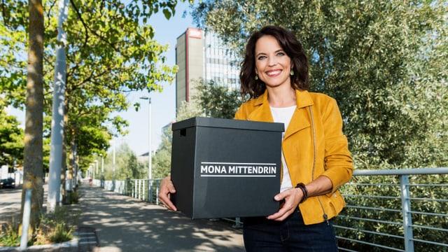 Moderatorin Mona Vetsch hält eine schwarze Schachtel in der Hand.