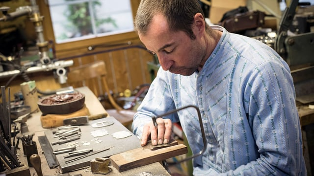 Ein Mann im Trachtenhemd beim Sägen in seiner Werkstatt.