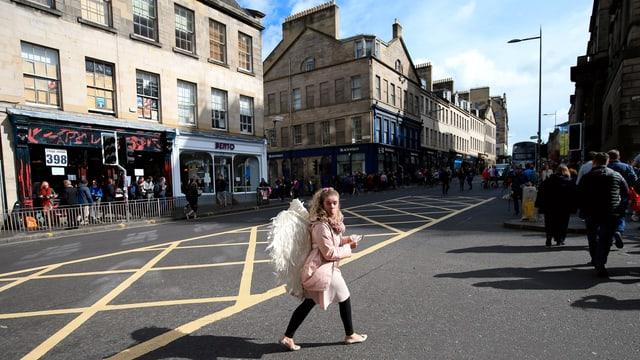 Eine Frau, die als Engel verkleidet ist, läuft in Edinburg über die Strasse.