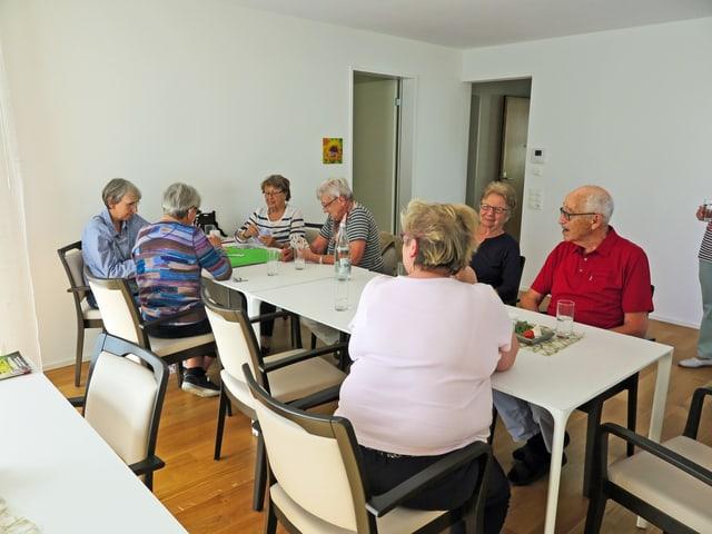 Eine Runde älterer Menschen sitzt um einen Tisch in der Siedlung Neuhushof. In dieser Siedlung wird grossen Wert auf die Durchmischung der Generationen gelegt.
