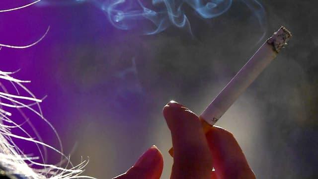 Maun che tegn ina cigaretta.