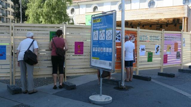 Eine Holzwand vor dem Luzerner Theater mit Gucklöchern, durch welche Menschen schauen.