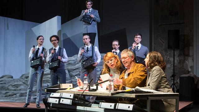 Vordergrund: Tisch mit Akten und drei Personen, Hintergrund: sechs graugekleidete Personen