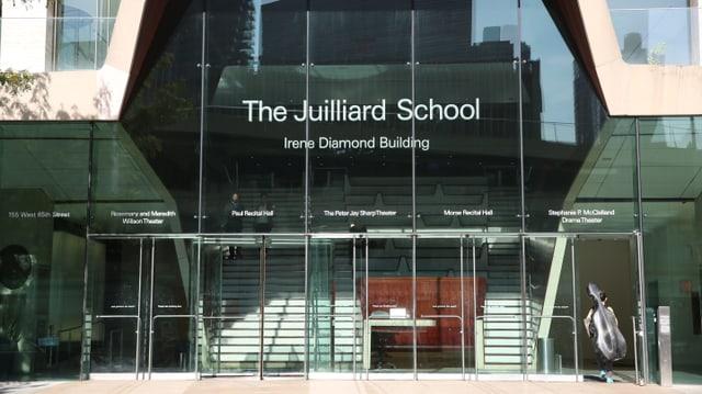 Ein Gebäudeeingang mit grossen Glastüren und -scheiben.