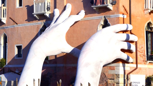 Die zwei weissen Hände greifen an die Fassade.