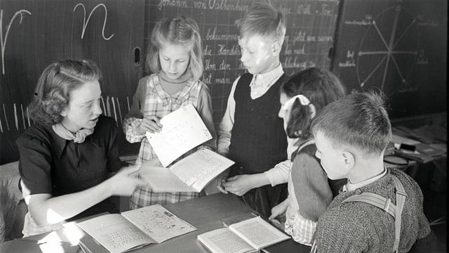 eine schwarz-weiss Fotografie einer Lehrerin, die ihren Schülern etwas am Pult zeigt