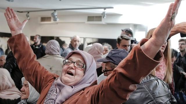 Eine Frau mit Brille und Kopftuch mit erhobenen Händen.
