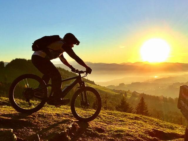 Biker in den Bergen während Sonnenaufgang.