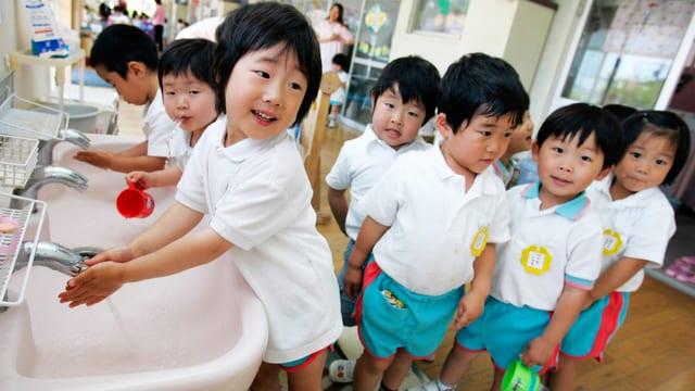 Japanische Kinder stehen vor dem Lavabo an. Sie sollen ihre Hände waschen.