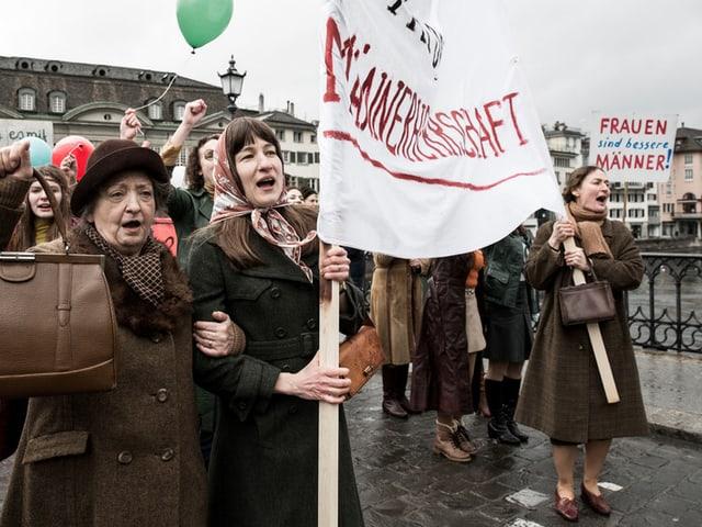 Filmstill: Frauen demonstrieren auf einer Brücke das Frauenstimmrecht.
