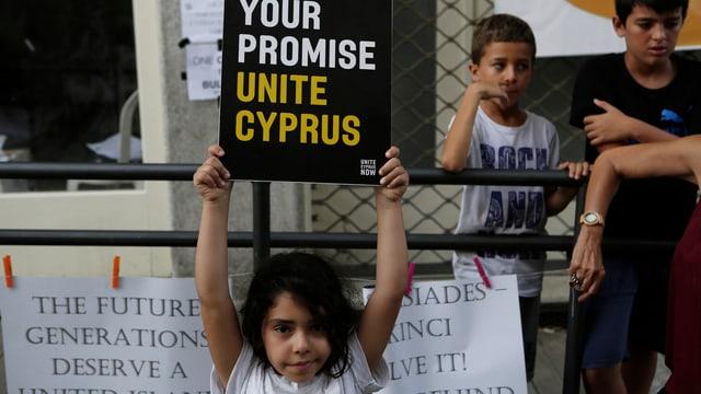 """Ein Mädchen hält ein Schild hoch, auf dem """"Unite Cyprus"""" steht."""