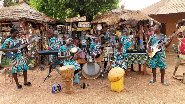 sieben junge schwarze Mädchen musizieren auf ihren Instrumenten