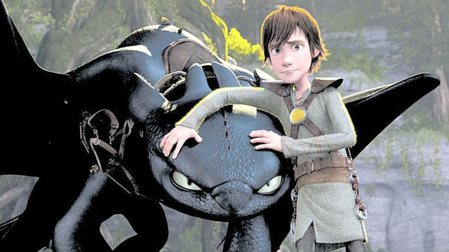 Der Wikinger Hicks hält schützend seine Arme über den Kopf eines Drachen.