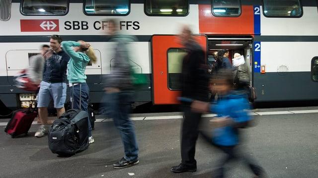 tren e passagiers en la staziun da viafier da Berna
