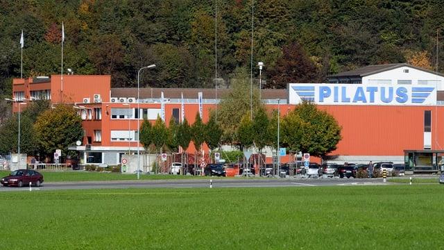 Orangefarbenes Fabrikgebäude mit Bäumen davor.