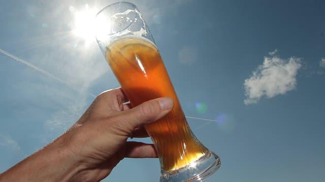 Eine Hand hält ein Glas Weissbier gegen die Sonne
