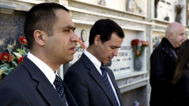 Jovan und José stehen vor einer Grabplatte mit Blumen.