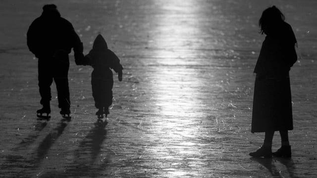 Ein Mann hält ein Kind an der Hand, beide tragen Schlittschuhe, daneben eine Frau ohen Schlittschuhe.