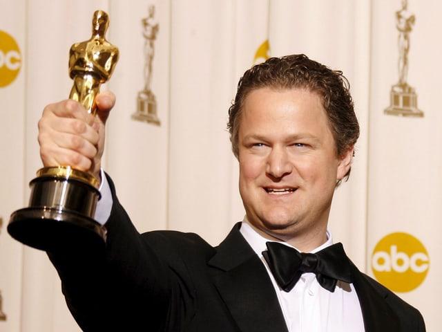 Ein Mann im Smoking hält stolz eine goldene Oscar-Statue in der Hand.