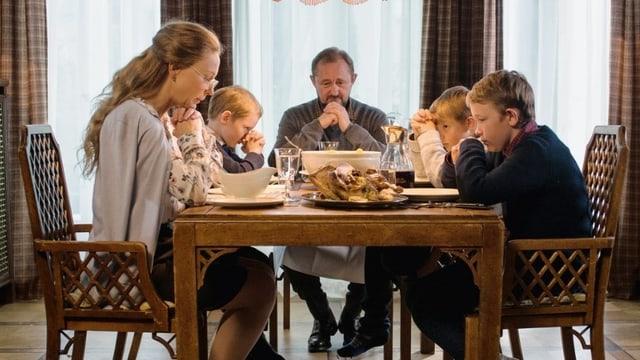 Eine Familie sitzt mit Händen zum Gebet gefaltet um den Esstisch.