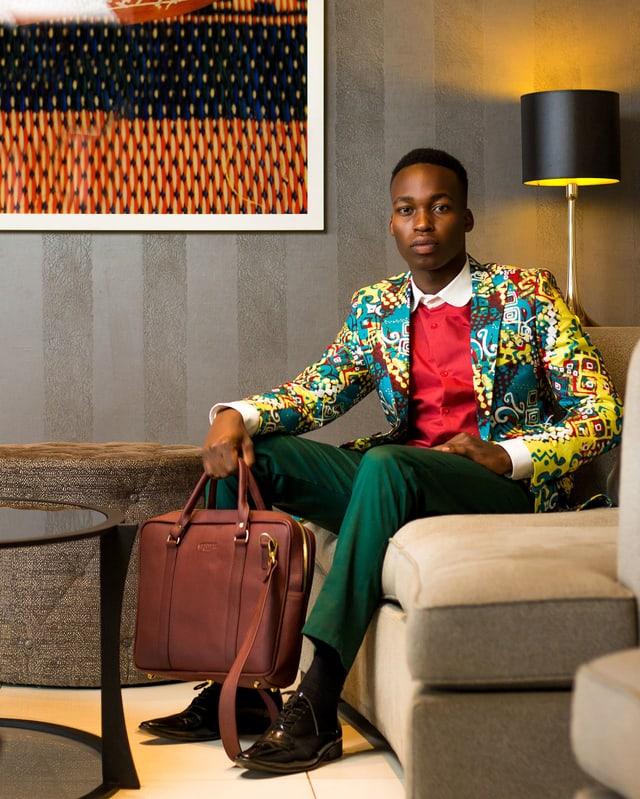 Ein junger Schwarzer in einem bunten Jackett sitzt auf einem Sofa.