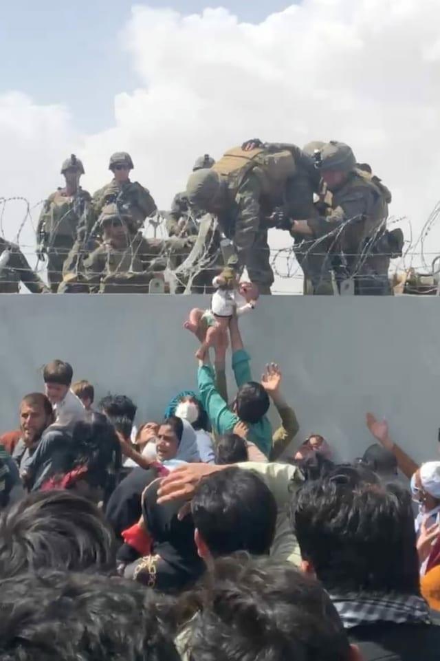 Mann übergibt Kleinkind an britische Truppen.