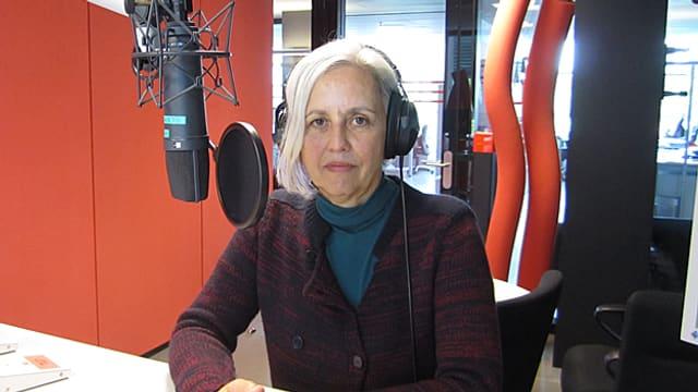Eine Frau mit halblangen, weissen Haaren sitzt vor einem Mikrofon